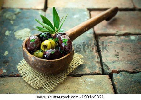 Variety of olives in an old wooden ladle with black, green and stuffed olives served as a savoury appetizer