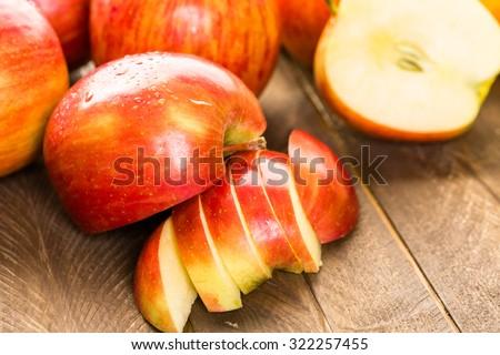 Variety of organic apples sliced on wood table.