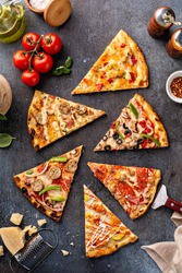 Variety of pizza slices with vegetarian, meat, hawaiian top view