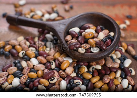 Variety of protein rich colorful raw dried beans on wooden table