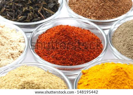 Variety of raw Authentic Indian Spices Powder on glass bowl isolated on white background in full-frame. Focus on chilli powder.