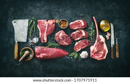Variety of raw beef meat steaks for grilling with seasoning and utensils on dark rustic board Stock photo ©