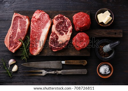 Variety of Raw Black Angus Prime meat steaks Blade on bone, Striploin, Rib eye, Tenderloin fillet mignon on wooden board and seasoning