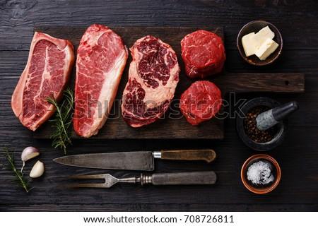 Variety of Raw Black Angus Prime meat steaks Blade on bone, Striploin, Rib eye, Tenderloin fillet mignon on wooden board and seasoning