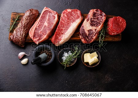 Variety of Raw Black Angus Prime meat steaks Machete, Blade on bone, New York, Rib eye, Tenderloin fillet mignon on wooden board and seasoning