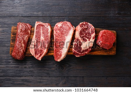 Variety of Raw Black Angus Prime meat steaks Machete, Blade on bone, Striploin, Rib eye, Tenderloin fillet mignon on wooden board copy space
