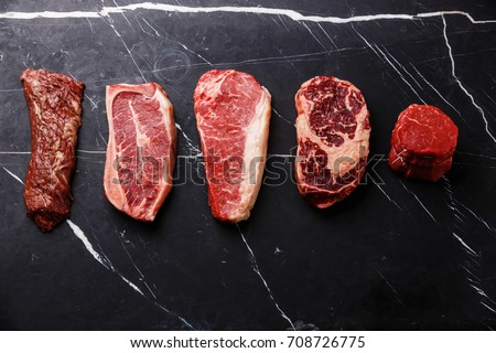 Variety of Raw Black Angus Prime meat steaks Machete, Blade on bone, Striploin, Rib eye, Tenderloin fillet mignon on dark marble background copy space