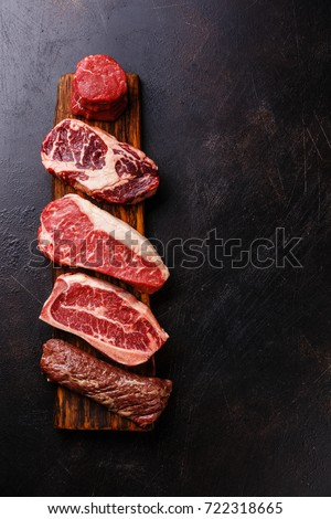 Variety of Raw Black Angus Prime meat steaks Machete, Blade on bone, Striploin, Rib eye, Tenderloin fillet mignon on dark background copy space #722318665
