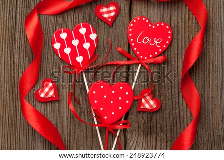 Variety of red hearts with ribbons on vintage wooden background for valentine\'s day holiday