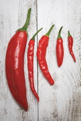 Variety of red, hot fresh organically grown chili peppers arranged from large to small, including Anaheim, Carolina Cayenne, Serrano and Dragon Cayenne varietys
