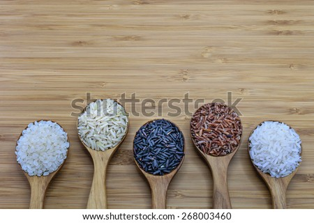 Variety of rice in wood spoon on wood background. From left: Japanese rice, pounded brown rice, forbidden rice (rice-berry), pounded red rice, jasmine rice