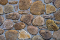 Variety of river rocks made into a exterior wall on a building surrounded by mortar for a rustic look closeup
