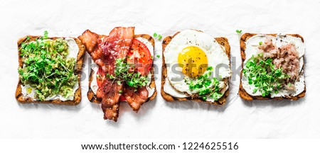 Variety of sandwiches for breakfast, snack, appetizers - avocado puree, fried egg, tomatoes, bacon, cream cheese, smoked mackerel grilled whole grain bread sandwiches. On a light background, banner