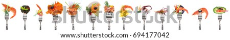 Variety of seafood appetizers on forks - white background