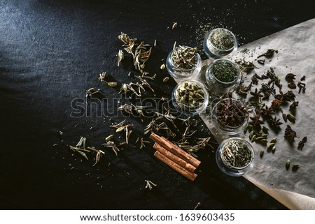 Variety of spices cinnamon, cardamom, anise, sugar and dry black tea over dark texture surface. Top view with space. Food background. Square image