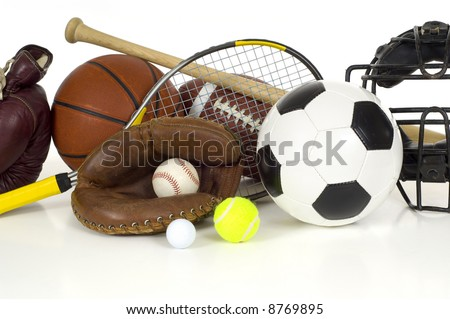 Variety of sports equipment on white background with copy space, items inlcude boxing gloves, a basketball, a soccer ball, a football, a baseball bat, a catcher\'s mitt or glove