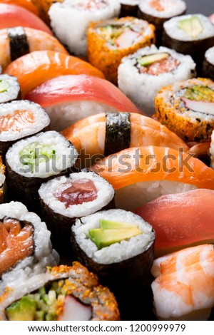 Variety of sushi food. Top view of nigiri, maki, hosomaki, uramaki and roll with tuna, salmon, avocado and shrimp. Traditional asian food with raw fish and rice. All you can eat concept.