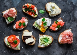 Variety of tapas sandwiches with prosciutto, avocado, salmon, egg, tomatoes, jamon, gorgonzola, brie, pear on a dark background, top view. Delicious snack, appetizers