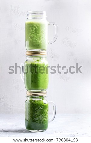 Variety of three color green spinach kale apple yogurt smoothie in mason jars on each other over gray background. Healthy vegan detox eating.