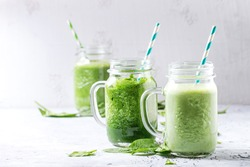 Variety of three color green spinach kale apple yogurt smoothie in mason jars with retro cocktail tubes over gray background. Healthy vegan detox eating.
