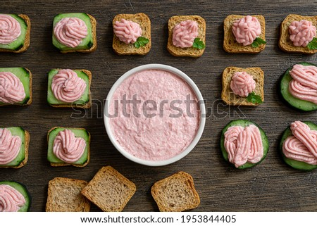Variety of toasts with tarama and white bowl with taramasalata on a dark wooden table, top view Stok fotoğraf ©