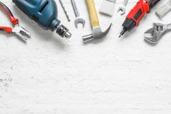 variety of tools for a constructions worker on the grunge white wooden background