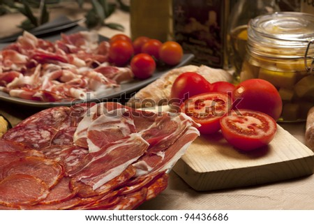 Variety of traditional spanish food: omelette, cured ham, chorizo, tomatoes, olive oil...
