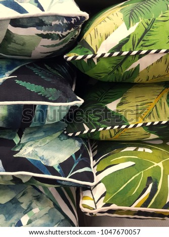 Variety of tropical patterned cushions stacked, on display for sale.