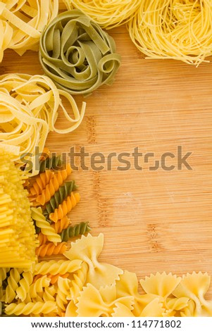 Variety of types and shapes of Italian pasta on wooden table