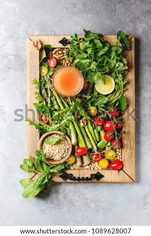 Variety of vegetarian healthy eating food ingredients. Green asparagus, herbs, tomatoes, nuts, wheat corns, dandelion leaves, glass of juice on wood tray over grey texture background. Top view, space. #1089628007