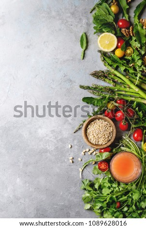Variety of vegetarian healthy eating food ingredients. Green asparagus, herbs, tomatoes, nuts, wheat corns, dandelion leaves, glass of juice over grey texture background. Top view, copy space. #1089628016