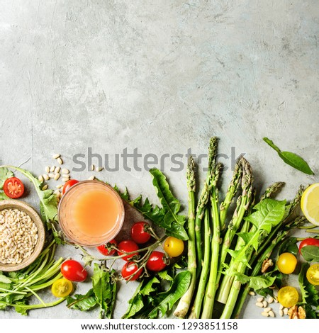 Variety of vegetarian healthy eating food ingredients. Green asparagus, herbs, tomatoes, nuts, wheat corns, dandelion leaves, glass of juice. Grey background. Top view, space. Square image #1293851158