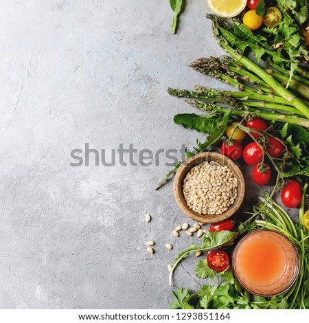 Variety of vegetarian healthy eating food ingredients. Green asparagus, herbs, tomatoes, nuts, dandelion leaves, glass of juice over grey texture background. Top view, copy space. Square image #1293851164