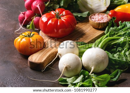 Variety of wet raw fresh organic colorful vegetables tomatoes, radish with leaves, fennel, paprika, salt for salad on wooden chopping board over dark brown texture background. Close up, copy space.