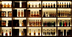 Various alcohol bottles in a bar, back light, all logos removed