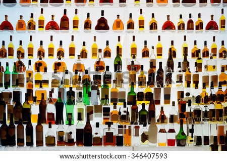 Various alcohol bottles in a bar, back light, all logos removed Foto stock ©