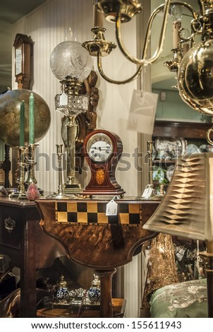 Various Antiques For Sale Viewed Through A Shop Window.