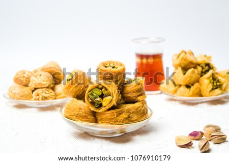 Various Arabic desserts with pistachio on plates #1076910179