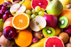 Various assorted juicy fruits: kiwi, orange, apple, grapes, grapefruit
