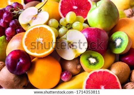 Various assorted juicy fruits: kiwi, orange, apple, grapes, grapefruit