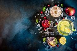 Various autumn winter seasonal alcohol cocktail Apple Rosemary, Cranberry vodka, Ginger lemon ale,  Almande Horchata, Kahlua Cacao, dark blue background copy space top view