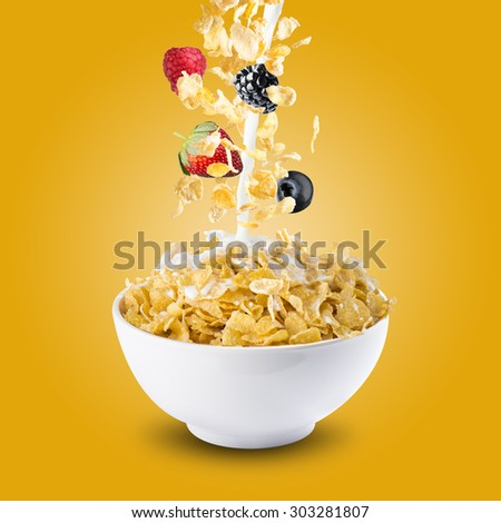 Various Berries Falling Into Bowl of Cereal With Milk Splash #303281807