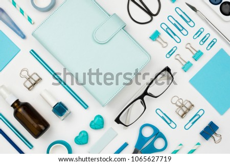 Various blue stationary and office tools and accessories knolled together on white: planner, pens, pencils, clips, glasses, scissors, etc. Flatlay - Shutterstock ID 1065627719