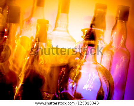Various bottles at a bar arranged in rows, motion blur