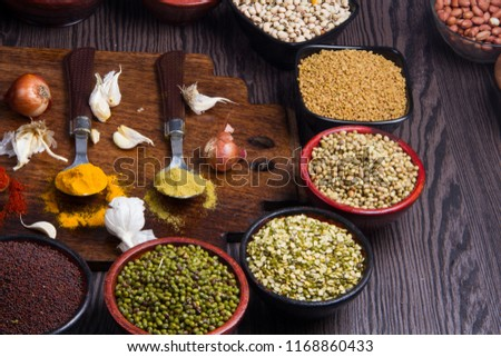 Various bowls of spices over wooden background. Colours and textures #1168860433
