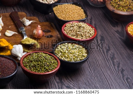 Various bowls of spices over wooden background. Colours and textures #1168860475