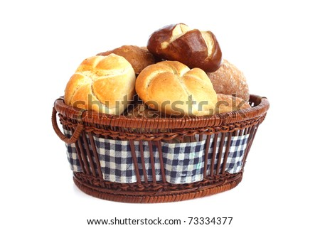 Various bread rolls in a basket against a white background