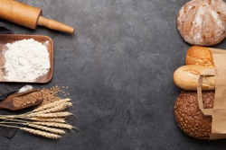Various bread with wheat, flour and cooking utensils on stone table. Top view flat lay with copy space