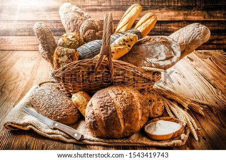 Various bread with wheat on old table in wooden wicker basket. Bakery food concept baker's ware photo. Foto d'archivio ©