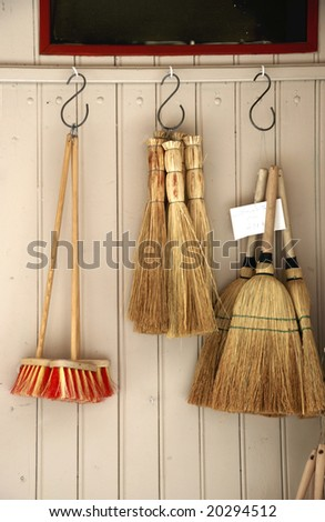 Various brooms hanging at the wooden wall of a house
